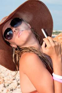 Frau mit Hut raucht eine Zigarette