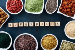 Bowls of various superfoods on old blue background. Top view